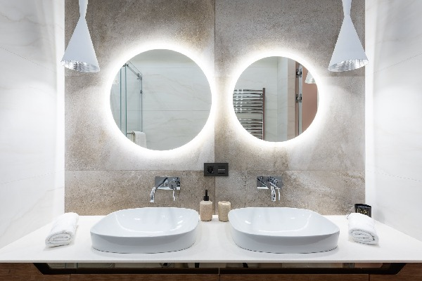 Washroom with lights behind the mirrors